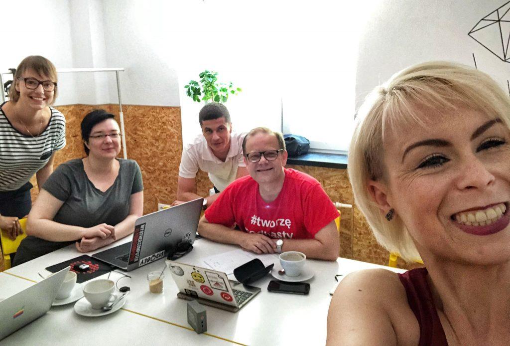 Pięcioro uśmiechniętych organizatorów przy laptopach i kawie.